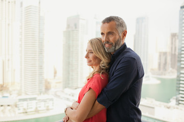 Couple embracing at balcony.