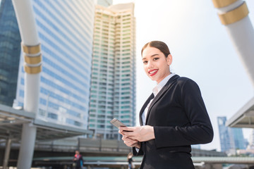 Modern smiling beautiful business woman using smart phone with copy space