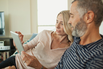 Couple using digital tablet at home.