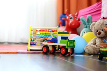 Children's multicolored toys on wooden floor or carpet on kids room