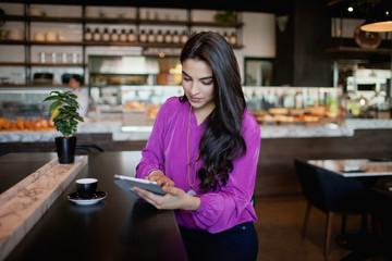 Woman using digital tablet at restaurant.