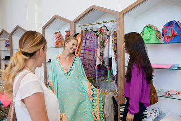 Women trying on dress at boutique.