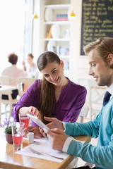 Couple using digital table in restaurant.