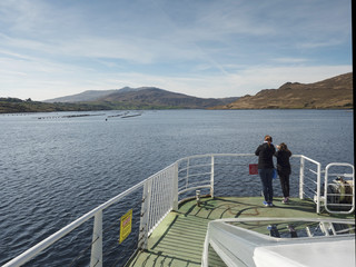 Mother and daughter looking at a mussels farm in a fjord from a bow of a cruise ship.