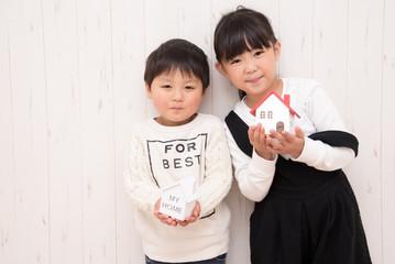 家の模型を持つ子供