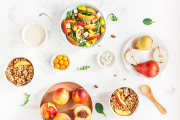 Breakfast with muesli, peach salad, fresh fruit, yogurt on white background. Healthy food concept. Flat lay, top view