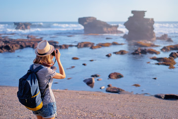 Traveling and photography. Young woman with camera and backpack taking picture on the sea beach.
