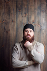 Confidence and manhood. Handsome young bearded man looking at camera on the wooden background