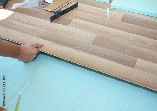 Contractor Installing Wooden Laminate Flooring With Insulation And