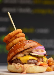 Gourmet craft bacon cheeseburger with chips and onion rings