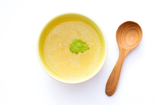 Bowl of chicken broth with wooden spoon isolated on white background