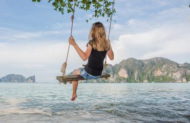 Girl on the seashore swinging on a swing