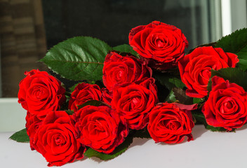 A  bouquet  of  red roses on a window, day light,  blurry background.