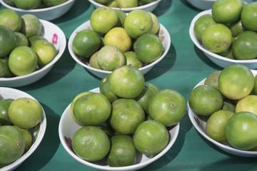 Green lemon on plate in the market.