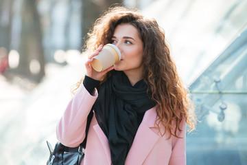Cute young woman drinking take away coffee.