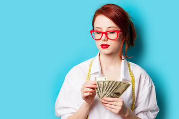 photo of beautiful young woman with money and centimeter on the wonderful blue background