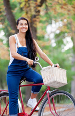 photo of beautiful young woman sitting on bicycle on the wonderful autumn park background