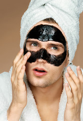 Handsome man applying black cosmetic mask. Photo of well groomed man receiving spa treatments. Beauty & Skin care concept