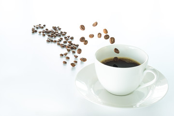 Coffee beans jumping into a white coffee cup