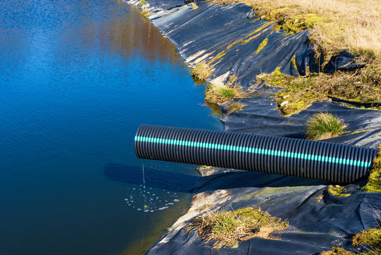 Landfill leachate pouring into pond from a black and blue pipe. Location Ronneby, Sweden.