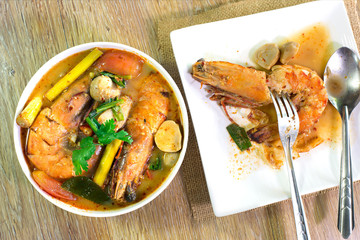 Prawn from Tom yum kung in white bowl with fork and spoon on wooden table