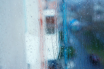 Textures of water droplets of rain flow down the windowpane. Condensation, high humidity , large drops of water, cold tone, natural water droplets on clear glass. Natural water drop background