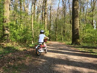 Fototapeta Kind mit Helm beim Radfahren im Frühling im Wald