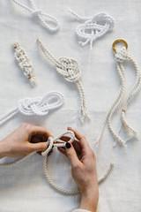 Hands creating yarn knots on tabletop