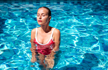 Summer vacation and relaxation. Beautiful young woman in red swimsuit at swimming pool.