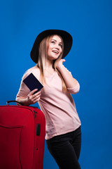 Beautiful young girl with a suitcase and a camera on a blue background