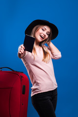 Beautiful young girl with a suitcase and a passport on a blue background