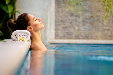 Beauty and body care. Sensual young woman relaxing in outdoor spa swimming pool.