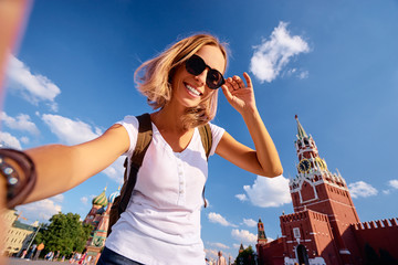 Travel and technology. Happy young woman taking selfie on Red Square in Moscow, Russia.