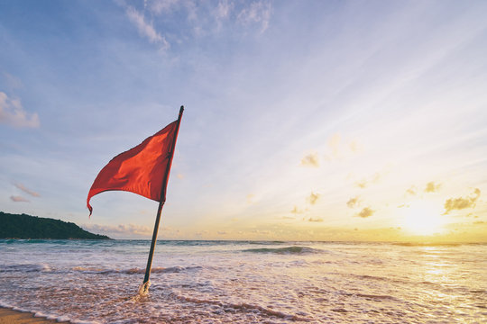 Beautiful sunset on tropical sand beach with red rescue flag.