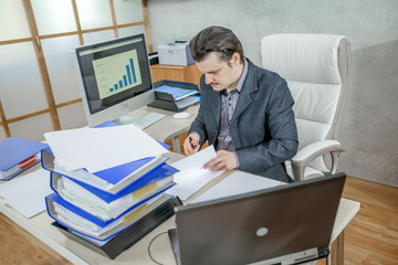 A young businessman is writing something on the documents in his office.