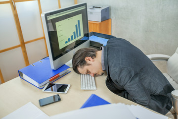 A young businessman is falling asleep after a tiring day in the office.