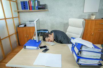 A tired businessman fell asleep on his keyboard. He worked hard all day.