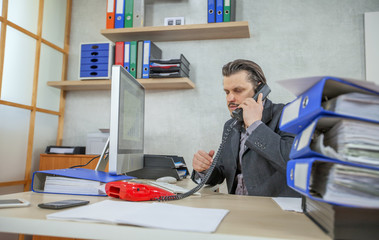 A young businessman is talking to a client on the phone. He is working in his office.