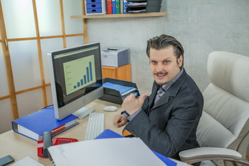 A happy businessman is having a thumbs up. He is working in his office.