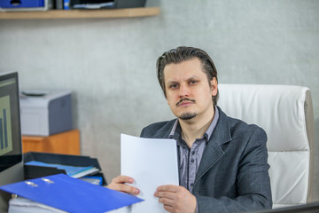 A young businessman is giving a serious expression. He is dealing with paper work.