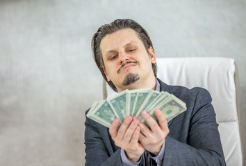 A businessman is having a smile on his face when looking at all the money in his hands.