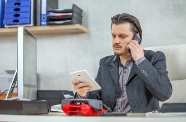 A businessman is talking on one cell phone and he is having another one in his hand.