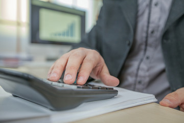 A businessman is typing on the calculator in his office.