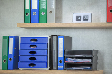 We can see nicely organized folders on the shelf. Some of them are green and some are blue.