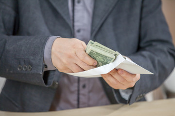 A businessman is putting American dollars into a white envelope.