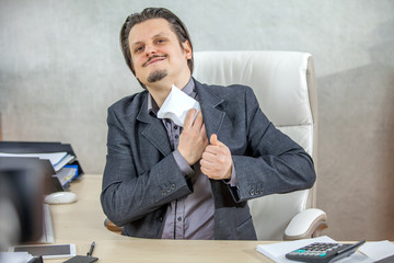 A businessman is putting an envelope with money in his business suit jacket.