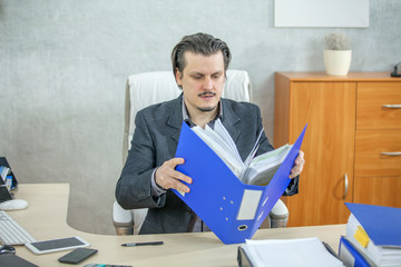 A young businessman is opening a big blue folder to check something in it.