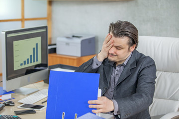 A businessman is looking exhausted when dealing with paperwork in his office.