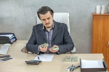 A young businessman is being serious when he is counting the American dollars in his hands.