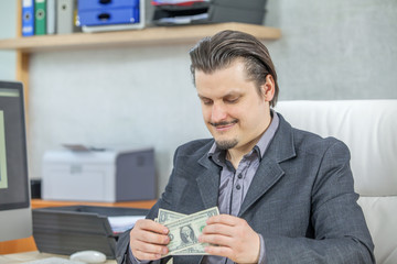 A young businessman is having a feeling of happiness on his face when having money in his hands.